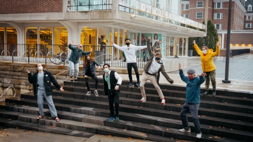 Hanover-based cast and crew of Faith, Hope, and Charity posing dramatically on Hopkins Center steps, masks on.